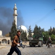 A rebel with the Free Syrian Army reacts