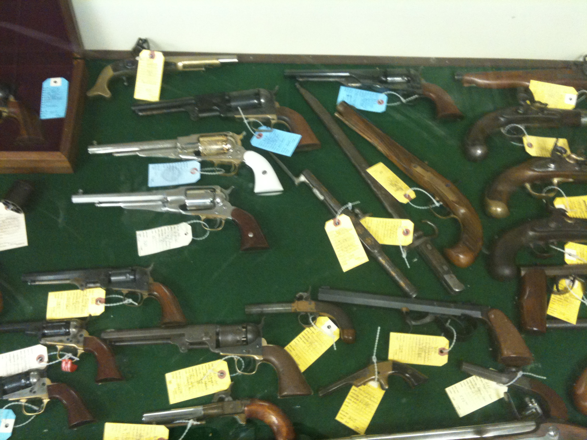 An assortment of revolvers and single shot handguns ranging from rare to reproductions. The blue tags represent NIB firearms while the yellow tags represent pre-owned.