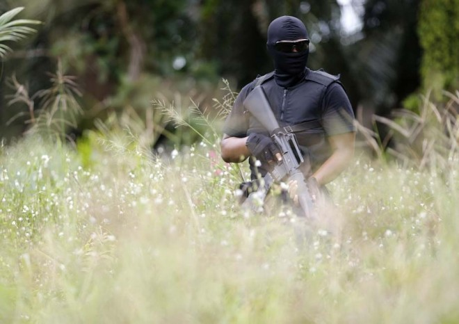 A special police force guards the area near the location where armed men are holding off in Lahad Datu