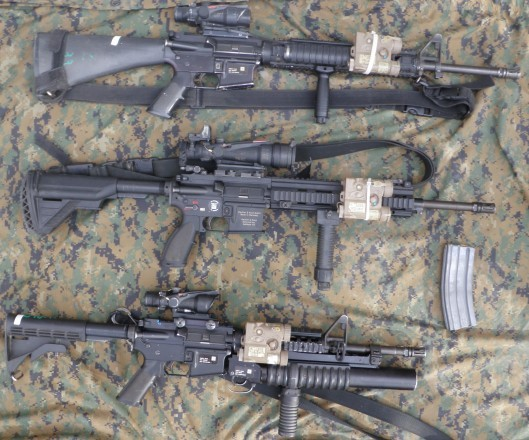 Displayed are three of the Marine Infantry squads current issue weaponry; M16A4 for riflemen, M27 for IAR gunners, and M4s with M203s for team and squad leaders. The M27 and M16A4 displayed have 3 point slings while the M4 has a 1 point. M4 and M27 have their stocks fully extended. Positioning of the laser emitting PEQ16 is up to the individual Marines discretion.