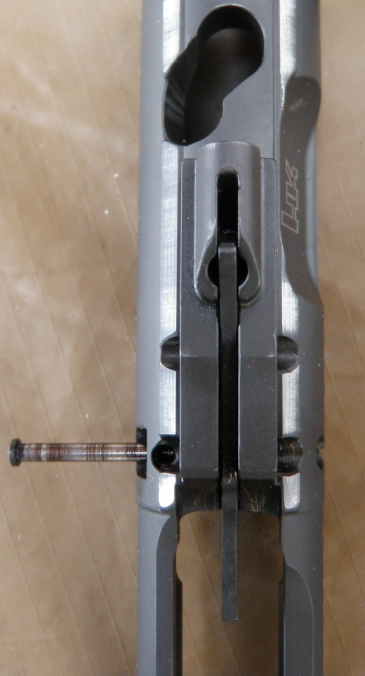 Top view of bolt carrier with captive spring fully extended. The large lever on top of the carrier serves two purposes: to keep the firing pin secure during disassembly and it acts as an internal safety. It prevents full travel of the firing pin unless it is struck by the hammer which pushes it up and the firing pin forward.