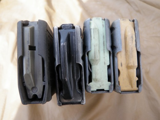 Close up display of magazine followers. From left; PMAG, H&K steel, original follower, tan anti-tilt follower. Issued STANAG magazines and those without the tan anti-tilt follower often have difficulty being inserted. The anti-tilt magazines were also introduced with the M27 in mind because the rate of fire was too much to keep up to with the previously standard issue magazines. Interestingly enough, H&K steel 30 round magazines have no issues whatsoever and in fact, are drop free unlike the others.