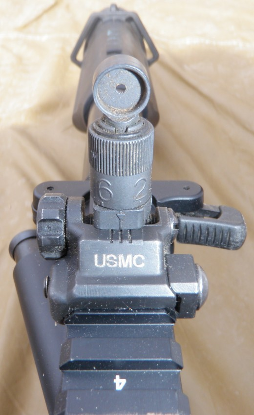 The rail mounted BUISs are Knight's Armament Corporation Flip Up Front Sight and the Micro Flip Up Rear Sight. Iron sights are peep hole types with a blade and protecting ears on the front sight. The rear sight is graduated from 200-600 meters with a Z setting for zeroing adjustments. Note USMC marked on front end. Also see the two pins on charging handle that can switch the lever to either side. Sling mounts are ambidextrous as is seen from this angle.