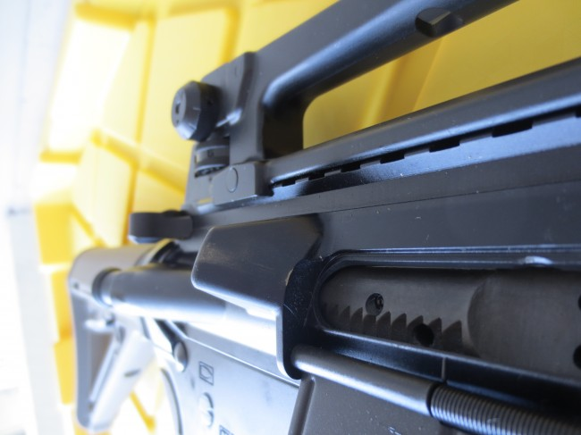 The handle extends about as far as the forward assist on a mil-spec AR.