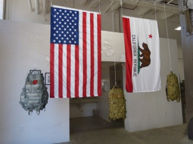 The American and California flags alongside TAD backpacks welcome visitors at the store entrance.