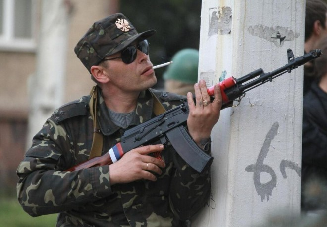 "A man in Ukrainian military uniform with colonel insignia, with the Russian coat of arms on his hat, holds a ""Russian Red"" AK-74 with a Russian flag on it. A red flashlight is seen taped to the hand guards."