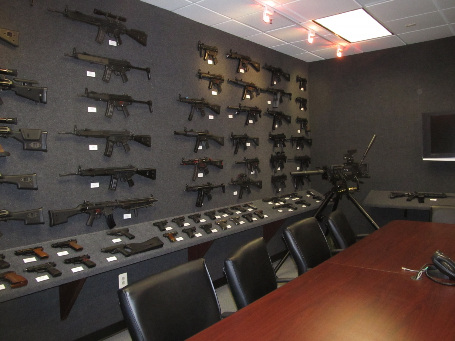 Left half of the room, literally nothing but MP5 and G3/HK33 models. The handguns are laid out on a table that circles the walls and the rifles are placed on nails that hold them in place but can be taken off to handle. It is also a working conference room with a center table and TV on the wall. Notice also the various models of the VP70 on the lower left.