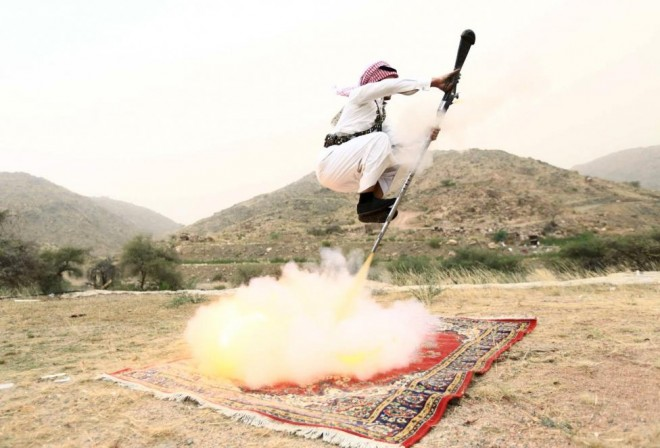A man fires a weapon as he dances during a traditional excursion near Taif, Saudi Arabia August 8, 2015. Saudis usually participate in such excursions as they celebrate weddings or graduations. REUTERS/Mohamed Al Hwaity