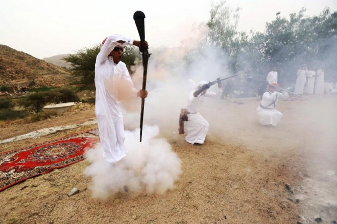 A man fires a weapon as he dances during a traditional excursion near the western Saudi city of Taif, August 8, 2015. REUTERS/Mohamed Al Hwaity