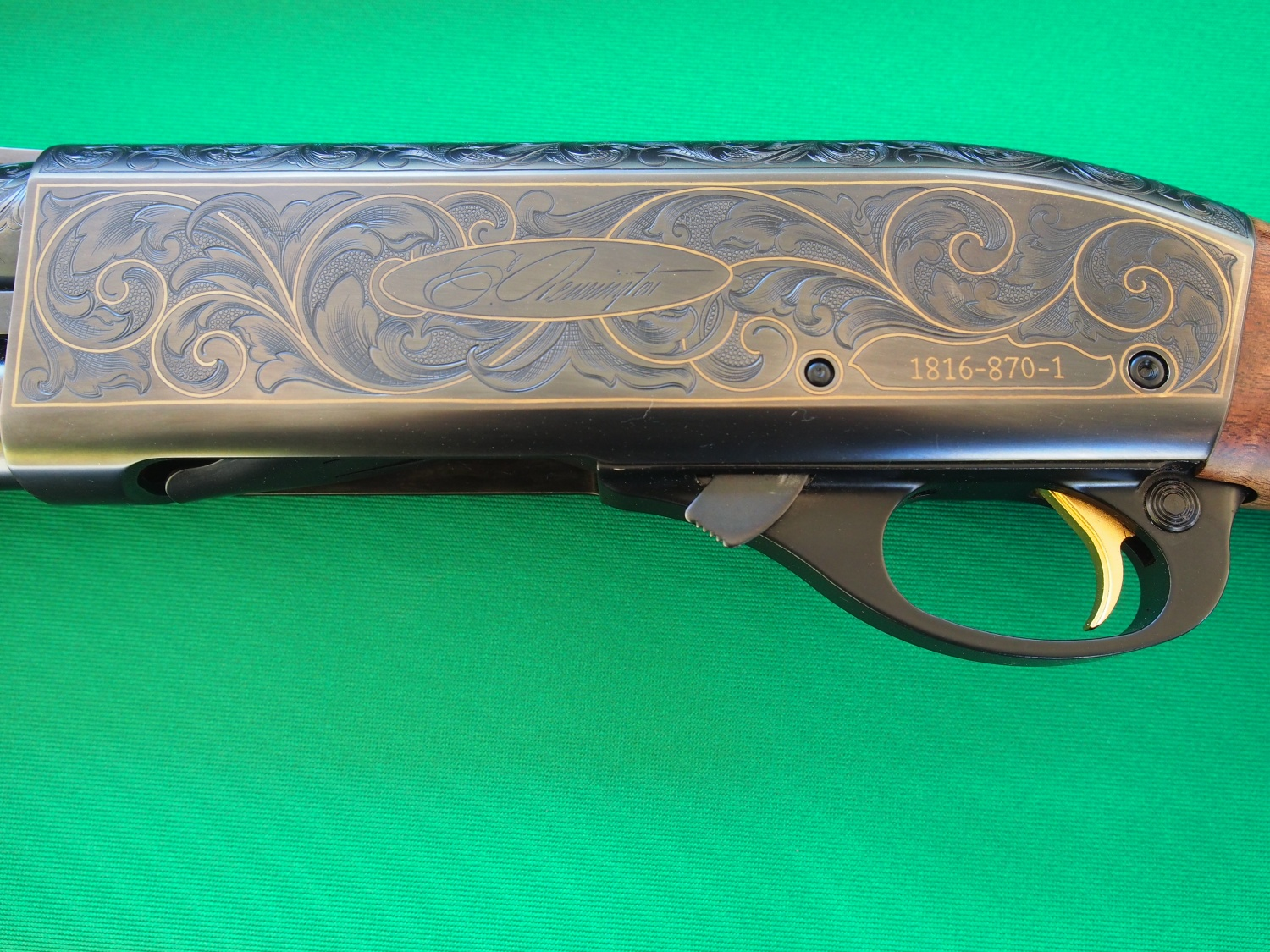 The left side of a high grade 870 with engraving covering the receiver and gold inlay throughout.