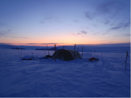 A camp at night up on the glacier, at that time of year and that far north there is practically 24 hours of daylight, on the final day of the trip we saw the sun set for the last time that year. Note one of the tripwire poles on the right hand side.