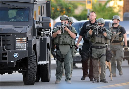 Authorities search an area Wednesday, Dec. 2, 2015, following a shooting that killed multiple people at a social services center for the disabled in San Bernardino, Calif. (James Quigg/The Victor Valley Daily Press via AP) MANDATORY CREDIT