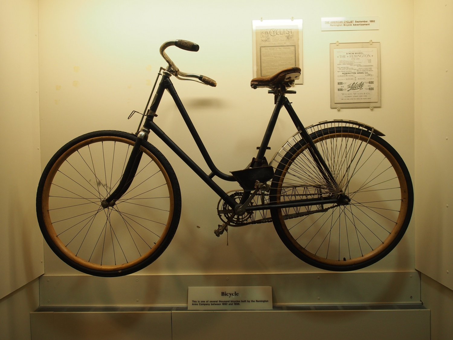 Remington bicycle. It has a tan leather seat and note the wheels are wood!