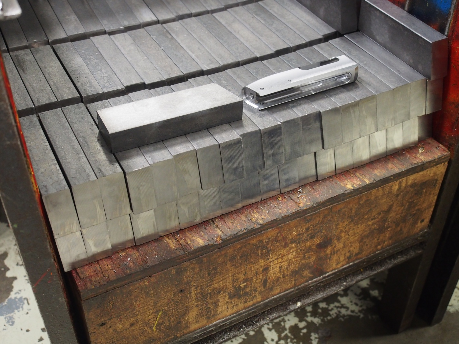 Blocks of raw material for shotgun receivers. One raw block shown next to a partially completed receiver. Each raw block weighs over 20 pounds.