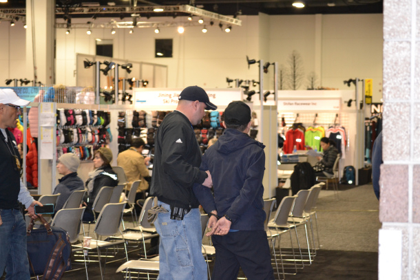 Guangzhou Botai U.S. representative and co-owner, Daniel Gong, being taken into custody on the showroom floor at the SIA Snow Show in Denver, CO.