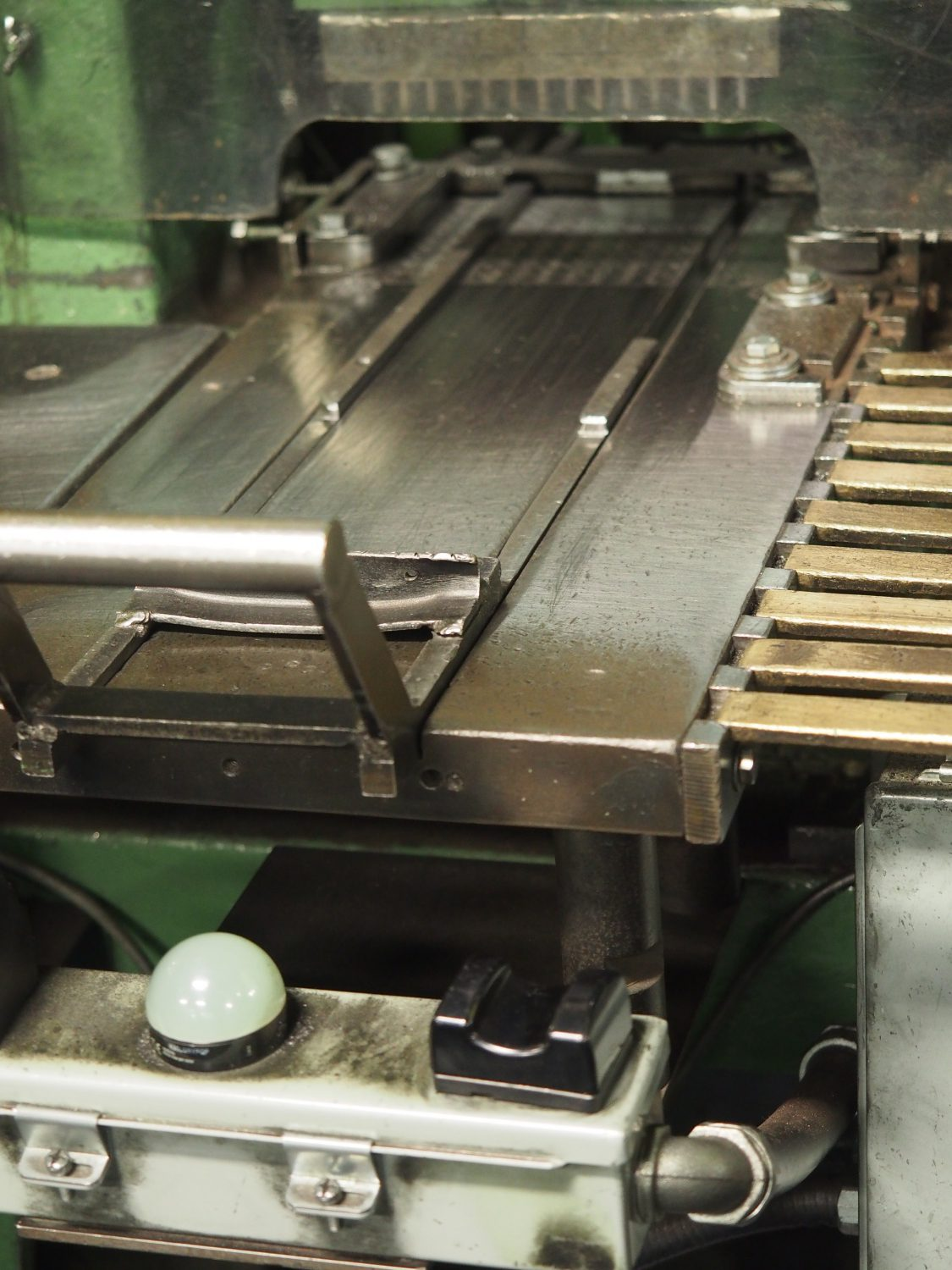 Trays are placed in front of these railed slides where the machine seats the bullets all in one stroke.