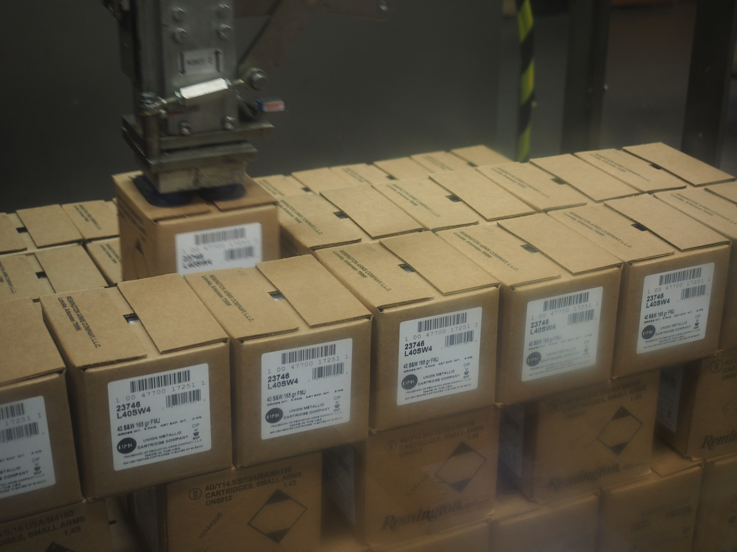 Robotic arm loading cases onto the pallet.