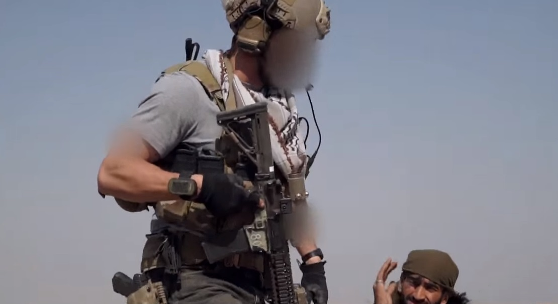 Complete tough guy image right here. The arm blurrings are for his tattoos. His Safariland is set much lower than any of his teammates. I would honestly be afraid of it breaking off at this point. Notice the EOTech despite all the recent controversy.