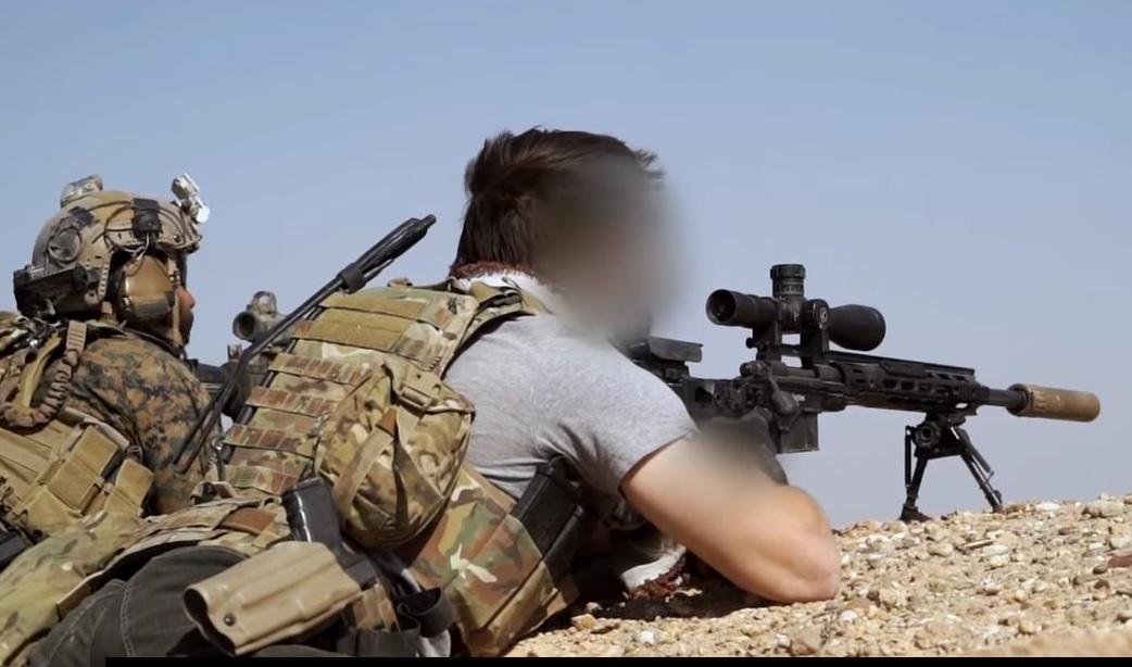 Remington M2010 ESR, with a Glock 17 holstered in a Safariland set up. M240 Lima with Elcan scope is what the gunner on the left is using. The sniper has his helmet off so he can get a better cheekweld on the rifle.