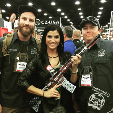 "Dana Loesch, center, holding the Axelson Tactical ""We The People"" rifle finished by Nevada Cerakote. Russ Bacon pictured on photo right."