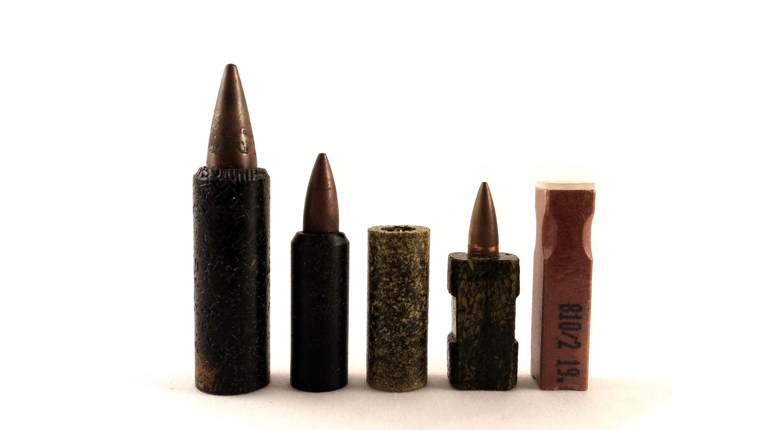 Caseless rounds, left to right: 7.62x34mm Frankford Arsenal caseless, 5.56x24mm FA caseless, 5.56x25mm Hercules caseless, 4.7x21mm H&K/DAG early caseless, 4.7x33mm HK/DAG G11 caseless.