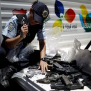 A police officer hammers a pistol during an exercise to destroy seized weapons in Caracas, Venezuela August 17, 2016. REUTERS/Marco Bello