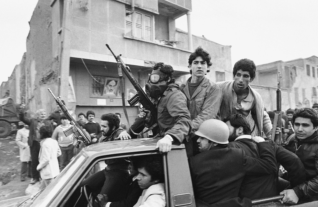 Armed rebels, one wearing a gas mask, ride in a truck near the headquarters of Ayatollah Khomeini, Feb. 12, 1979 in Tehran. (AP Photo)