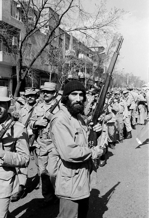 Troops of Iran's new Islamic National Guard, background, parade through the streets of Tehran, Feb. 26, 1979, in a show of support for the Ayatollah Ruhollah Khomeini, whose regime is facing a challenge by Iranian leftists.  In the foreground is a member of the leftist mujahedeen guerrillas.  (AP Photo)