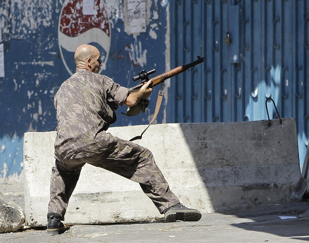 A Sunni gunman fires by his machine gun during clashes that erupted between pro and anti-Syrian regime gunmen in the northern port city of Tripoli, Lebanon, Friday, Aug. 24, 2012. The latest round of fighting first erupted on Monday in northern Lebanon and at least 15 have been killed in Tripoli this week and more than 100 have been wounded in fighting that is a spillover from Syria's civil war. (AP Photo/Hussein Malla)