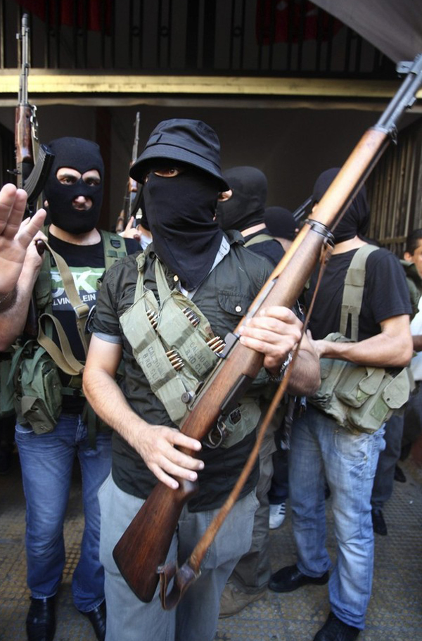 Shi'ite masked gunmen from the Meqdad clan, gather at the Meqdad family's association headquarters in the southern suburbs in Beirut, August 15, 2012. A Shi'ite Muslim clan in Lebanon has abducted a Turkish businessman and several Syrians it says are rebel fighters in retaliation for the kidnapping of one of their relatives by the rebel Free Syrian Army in Damascus. REUTERS/Khalil Hassan    (LEBANON - Tags: POLITICS CIVIL UNREST)