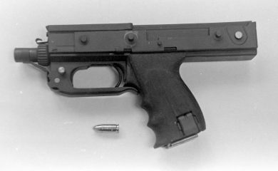 The sole Almara-designed MPA full-auto pistol prototype is seen here with a 9x19mm ammo round for size comparison.