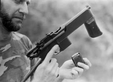 "The 10-round box magazine being inserted into the ""Mod.2"" PASAM, the action remaining open after the previous last shot. The 20-round unit, not supplied to Brazil, would have been more practical. Note distinct shape of the vertical fore grip with wooden side panels fitted to this example."