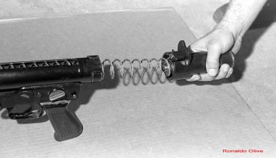 Removing the tubular receiver's rear end cap to allow the large diameter recoil spring to be pulled out.