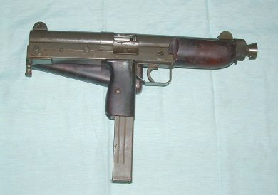Right side view of the BSM9/M1, spring-loaded ejection window cover open, with the wooden stock folded to the left. Magazine capacity is 32 rounds.