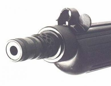 The barrel mounting nut featured an extension glove that doubled as a muzzle brake. Also clear in photo are the hooded front sight protection and the blade-type cocking piece just beside it.