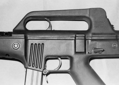 """This close-up view shows details of the gun's work area, with the fire selector set for """"S"""" (rear), the cocking piece within the AR-10-inspired carry handle (actually, the rear sight covering structure), and the blade-type magazine catch."""
