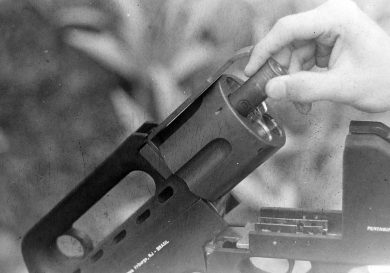 A 12-ga cartridge being loaded into the cylinder, above which is the part that locked into the rear latch to keep the gun firmly closed.