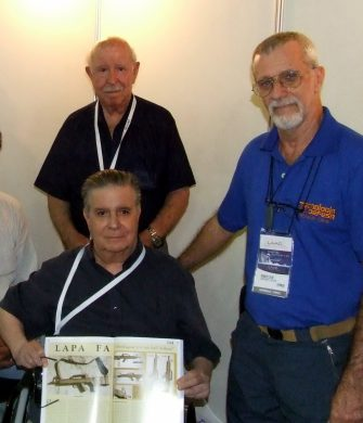 With long-time, trusted friend Luiz Gonçalves behind and lasting admirer Ronaldo Olive by his side, Nelmo Suzano poses with a Tecnologia & Defesa magazine article on his work during the LAAD Exhibition in Rio de Janeiro in April 2009, his last public appearance.