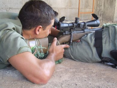 A Brazilian Army trainee learns how to use his spotter's butt in place of the AGLC bipod. The gun's stock is all-wood, and can receive butt spacers to adjust length.