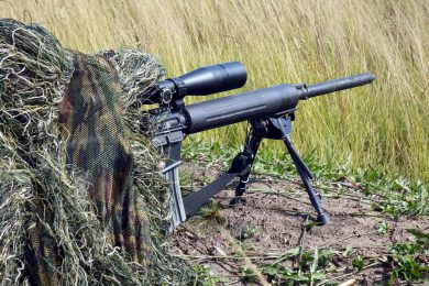 A BOPE sniper, Ghillie-suited for a possible action in a rural area of Rio de Janeiro State, takes aim with the sleek-looking Colt rifle. The cylindrical aluminum handguard is noteworthy, so is the barrel wrapped in rubber bands.