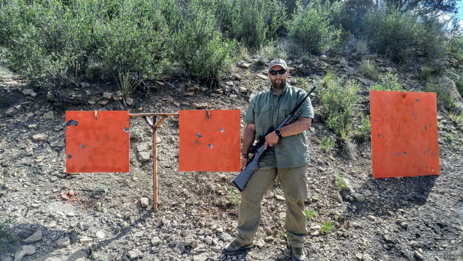 The author standing next to the plate at 1400 yards with the 22 Nosler m48 Liberty. The rounds still had enough power to take paint off the target.