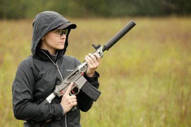 woman in field holding a rifle