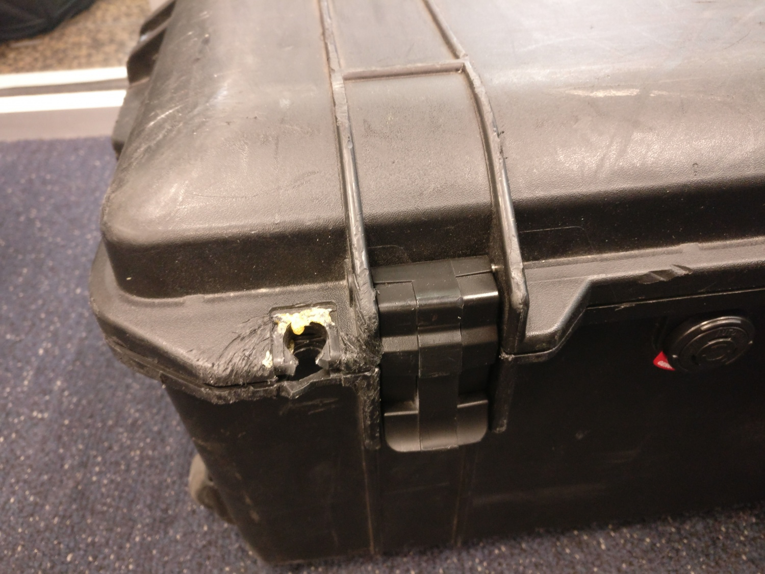 A broken hasp on one of the author's Pelican cases, which has been subject to repeated repair attempts.