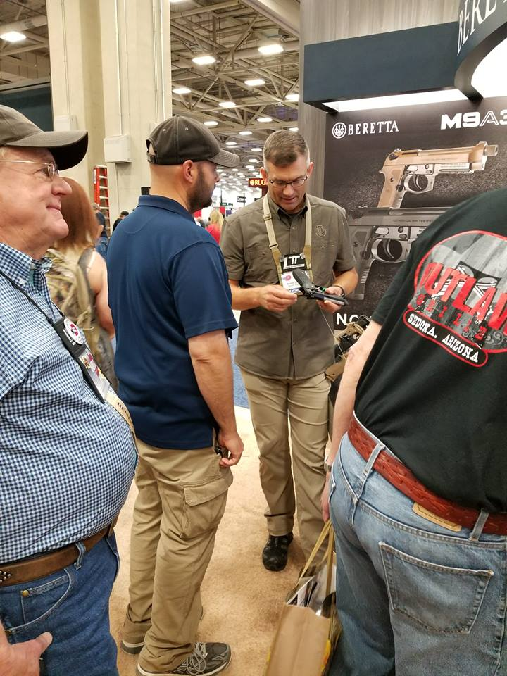 Ernest Langdon (brown shirt, center) goes over the differences between the M9A3 and the 92 Elite LTT at NRA 2018.