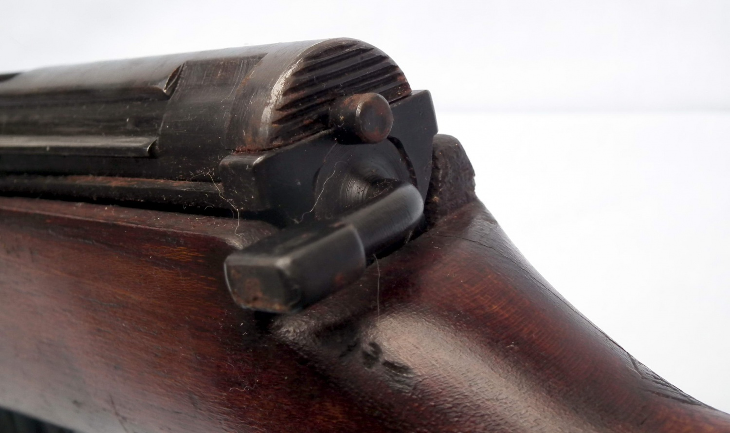 Seen from the rear, the rifle's bolt housing, and the applied safety lever.