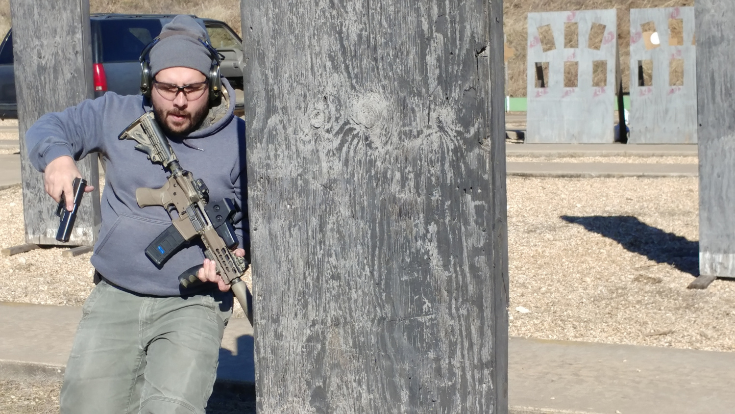 In this picture, the author had to transition to a Glock after that fancy M4 was out of ammo. Chambering a round one-handed, on the move, while getting to cover is possible, but completely unnessesary if you just carry a loaded gun.