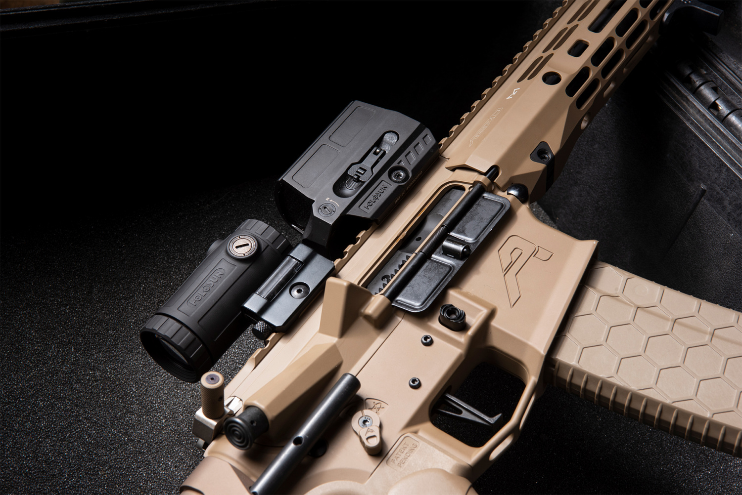 Here Holosun shows off their new magnifier mounted behind one of their 512 series reflex sights.