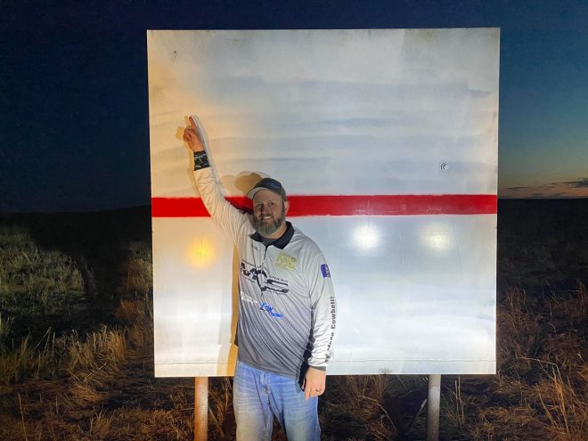 Extreme Long Range competition shooter Ryan Cheney proudly poses with his record-setting 2.35-mile impact.