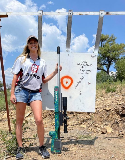 ELR shooter Lindsey Paul posing with her cold bore world record-setting rifle and target.